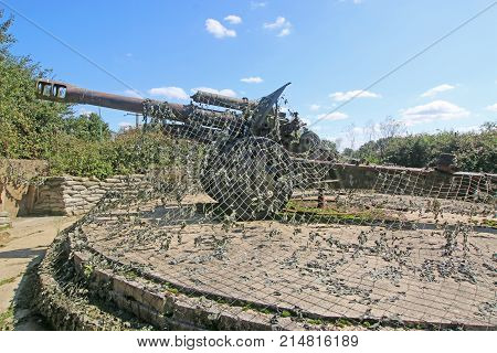 vintage German Field gun under camouflage netting