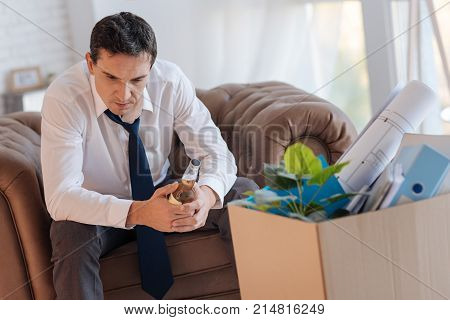 Redundant man. Thoughtful unhappy young specialist sitting in an armchair in front of a box with personal items and holding a bottle of alcohol in his hands