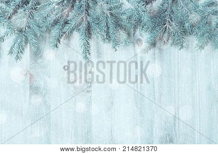 Winter background. Blue fir tree branches with winter snowflakes on the wooden background. Winter still life, free space for text. Colorful winter background. Winter composition
