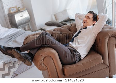 New job. Smiling cheerful young man relaxing in a comfortable armchair and feeling happy after getting a wonderful job in a good company