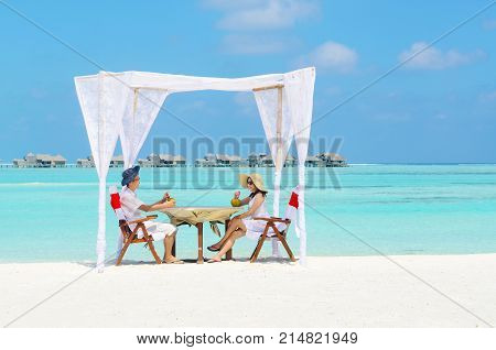 Asian couple in sunhat enjoying romantic luxury lunch setting at tropical beach in Maldives