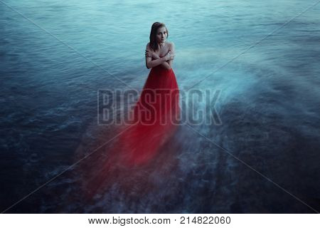 Lonely woman in red dress near the sea