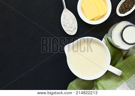 Homemade French Bechamel or White Sauce served in sauce boat with ingredients on the side (flour butter milk pepper) photographed overhead on slate with natural light (Selective Focus Focus on the sauce)