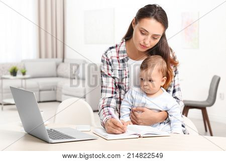 Young mother holding baby while working in home office