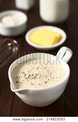 Homemade French Bechamel or White Sauce served in sauce boat with ingredients in the back (flour butter milk) photographed on dark wood with natural light (Selective Focus Focus one third into the image)