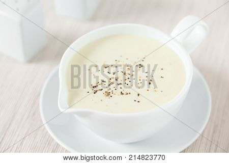 Homemade French Bechamel or White Sauce served in sauce boat photographed with natural light (Selective Focus Focus in the middle of the image)
