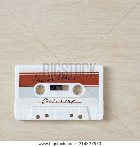 Vintage audio cassette tape with christmas songs on wooden background