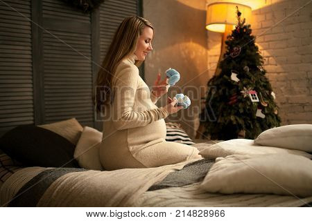 Pregnant woman sits before Christmas tree and looks at baby's bootees. She keeps them in hands. Light from lamp illuminates room.