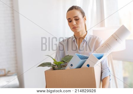Losing job. Sad quiet young woman looking calm and frustrated while coming home with a heavy box full of personal items after losing her job
