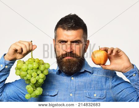 Winegrower With Serious Face Holds Grapes And Red Fruit.