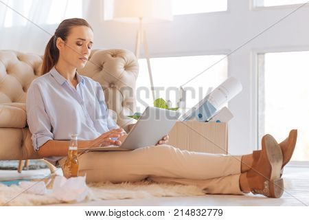 Attentive person. Responsible attentive enthusiastic woman sitting comfortably and typing a text while drinking alcohol at home
