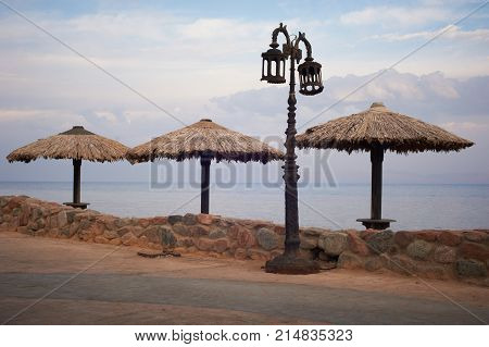 Empty embankment with straw umbrellas and streetlights in Dahab.