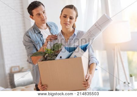 No worries. Emotional tired sad woman carrying a big box of personal items after being fired from work while her kind attentive husband persuading her not to worry