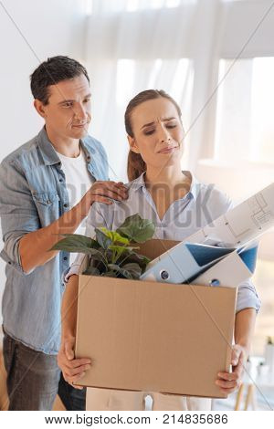 Not important. Emotional sad dismissed woman standing with a box of personal items and trying not to cry while her loving husband helping her to overcome this hardship