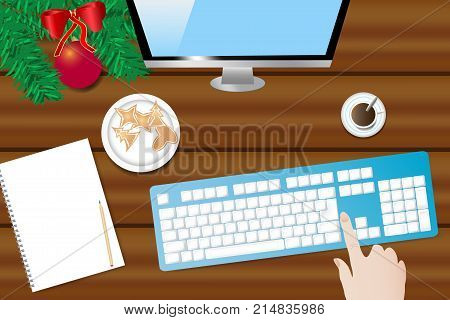 Top view of the wooden desk with Christmas decoration coffee cup blank paper with pen ready for your text computer monitor and keyboard. Hand is touching keyboard.