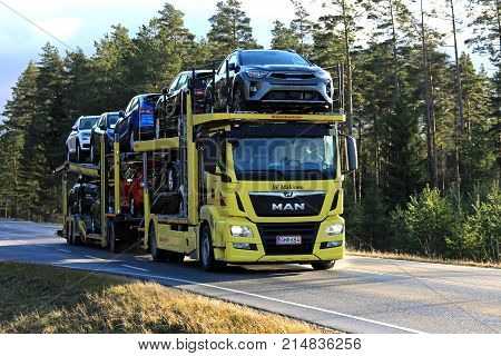 SALO FINLAND - NOVEMBER 17 2017: Yellow MAN TGS 18.420 car carrier of SE Makinen hauls new cars along highway in late autumn.