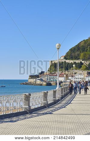 San Sebastian (Donostia) Spain - March 16, 2017. People walking in Miraconcha Avenue with Donostia fishing port and Monte Urgull in background. Basque Country Guipuzcoa. Spain.