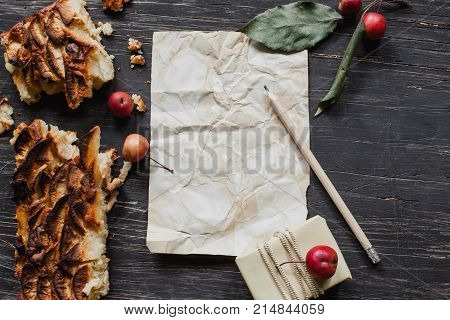 Apple tart with small apples and leaves on black wooden table with wish list and pencil