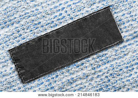 Blank black textile clothes label on white and blue cloth as a background