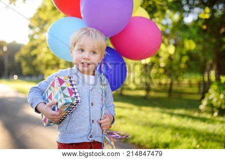 Cute Boy Holding Bundle Of Colorful Balloons And Gift In A Festive Box. Happy Birthday!