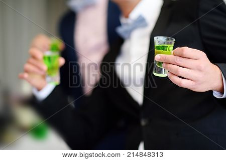 Groomsmens holding alcoholic cocktails. Groom and best man drinking strong alcohol (absinthe liqueur) during wedding party poster