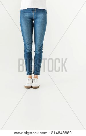 low section of young woman in denim pants and shoes standing isolated on white