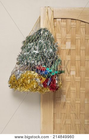 Mesh bag full of tinsel, lights for christmas tree hanging on the wooden door