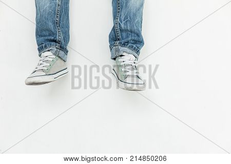 low section of child in jeans and shoes posing isolated on white