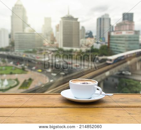 White coffee cup on wood table beside the window which can see the abstract Blurred photo of sky train with cityscape background business traffic in rush hour concept