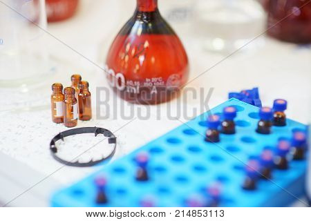 Glass laboratory tubes, vials and test tubes for collecting samples and conducting tests close-up on a table in the laboratory. Pharmaceuticals and medicine. Soft focus.
