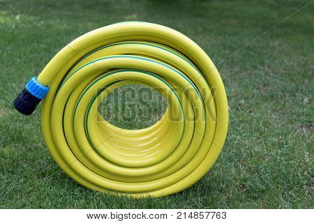 Yellow plastic hose pipe on a grass