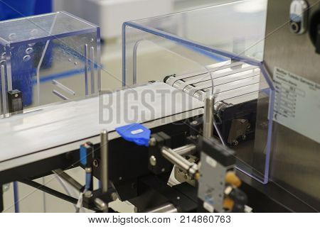 Part of the production line or conveyor close-up. Mechanical tape conveyor for the production and packaging of medical products. Soft focus.