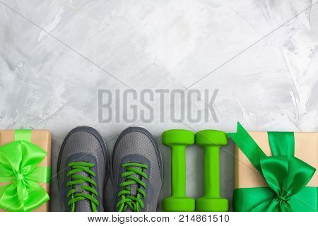 Holiday christmas birthday party sport flat lay composition with gray shoes green dumbbells and craft gifts with green bow on gray concrete background. Top view horizontal orientation