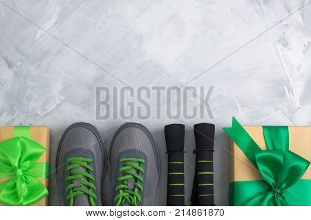 Holiday christmas birthday party sport flat lay composition with gray shoes black dumbbells and craft gifts with green bow on gray concrete background. Top view horizontal orientation