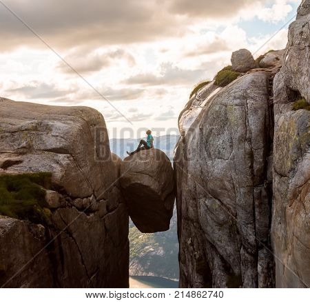 Woman on Kjeragbolten Travel in Norway Kjerag mountains, extreme vacations, adventure, tourist, happy emotions, success concept