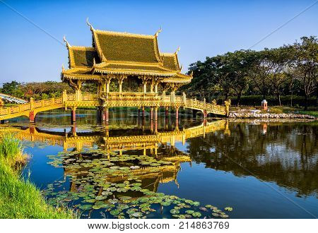 Amazing view of beautiful Golden Bridge and Pavilion of the Enlightened with reflection in the water. Location: Ancient City Park Muang Boran Samut Prakan province Bangkok Thailand. Artistic picture. Beauty world.