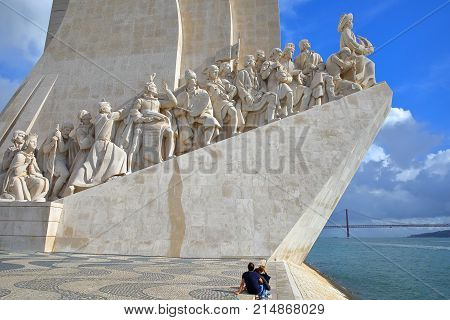 LISBON, PORTUGAL - NOVEMBER 3, 2017: A tourist couple watching the Monument of the Discoveries (Padrao dos Descobrimentos) located in Belem neighborhood beside the Tagus river