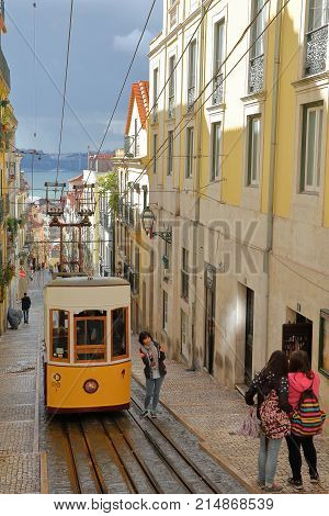 LISBON, PORTUGAL - NOVEMBER 4, 2017: The funicular Elevador da Bica in Bairro Alto neighborhood with Japanese tourists taking pictures and Tagus river in the background