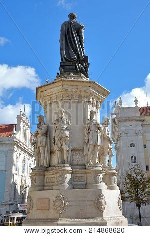 LISBON, PORTUGAL - NOVEMBER 4, 2017: Close-up on Luis de Camoes poet statue at Camoes Square in Bairro Alto neighborhood with two churches (do Loreto on the left and da Nossa Senhora da Encarnacao on the right) in the background