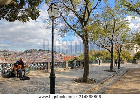 LISBON, PORTUGAL - NOVEMBER 4, 2017: Sao Pedro de Alcantara viewpoint (Miradorou) in Bairro Alto neighborhood with a musician singer in the foreground and the city in the background