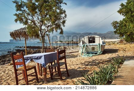 Greek tavern table and motorboat on the beach on the island of Crete