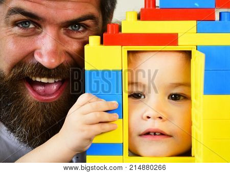 Boy and man play together close up. Father and son with happy and serious faces hold colorful toy bricks construction. Toys and childhood concept. Dad and kid hide behind house made of plastic blocks