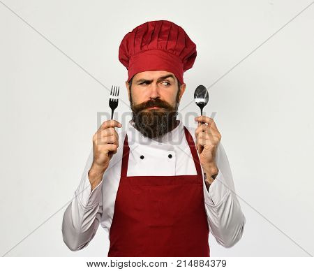 Cook With Confused Face In Burgundy Uniform Shows Cutlery