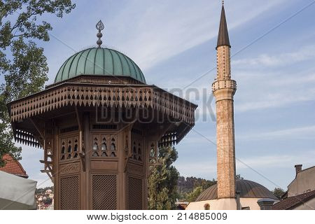 SARAJEVO, BOSNIA AND HERZEGOVINA - AUGUST 18 2017: Architectural close up of the top of Sebilj fountain and mosque minaret in Sarajevo city centre