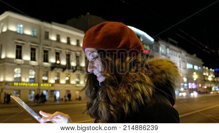 Young girl with tablet looking at the screen and fingertip and smiles. On the background of night city, moving cars and walking crowds of people
