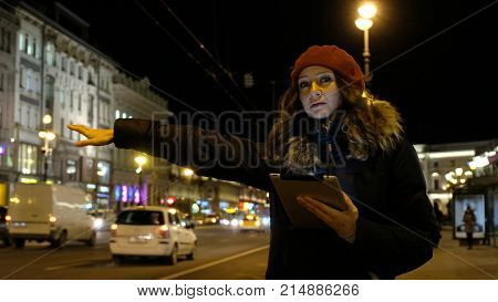 Young Caucasian girl with tablet in hand looking at the screen and waits and stops the bus, comes in. On the background of evening city.