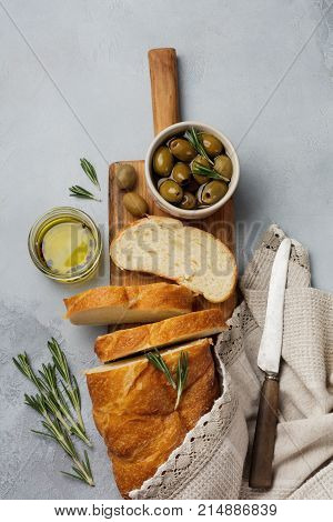 Italian traditional Ciabatta bread with olives olive oil pepper and rosemary on light gray stone or concrete background. Selective focus.Top view. Copy space.