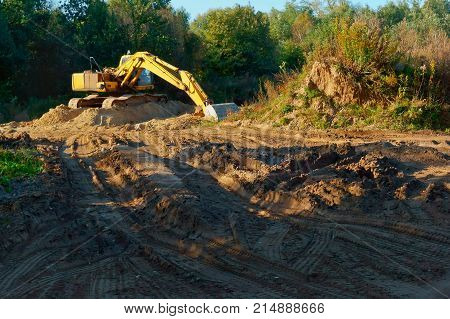 excavator digs the ground in the woods, laying of pipelines, destruction of the soil