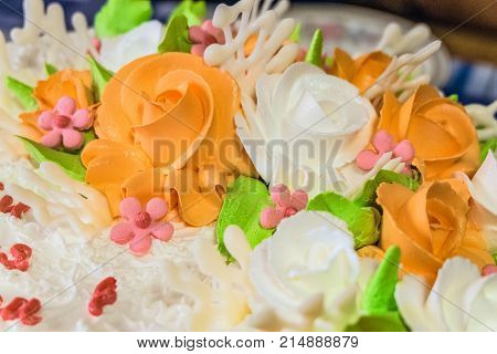 Sweet whipped cream orange and white roses. Cream cake background with limited depth of field.