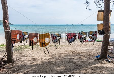 Colorful life jackets is hanging on the rope for rent to the tourism near the beacheastern coast of Thailand.